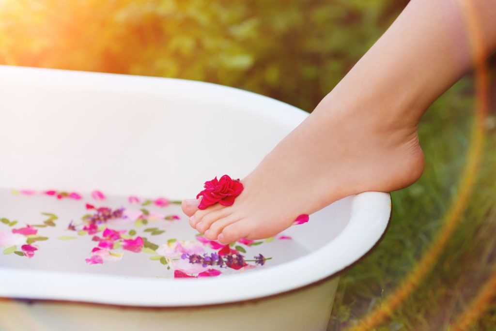 Woman placing foot on tub