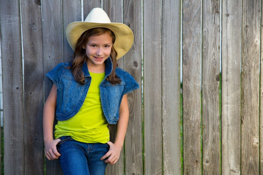 cowgirl posing on wooden fence