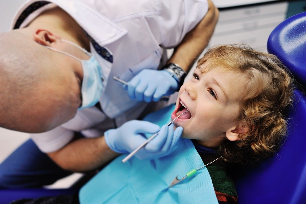 Dentist checking young boy's teeth