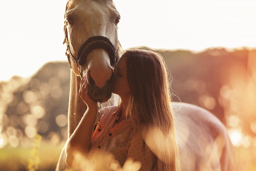 cowgirl kissing her horse