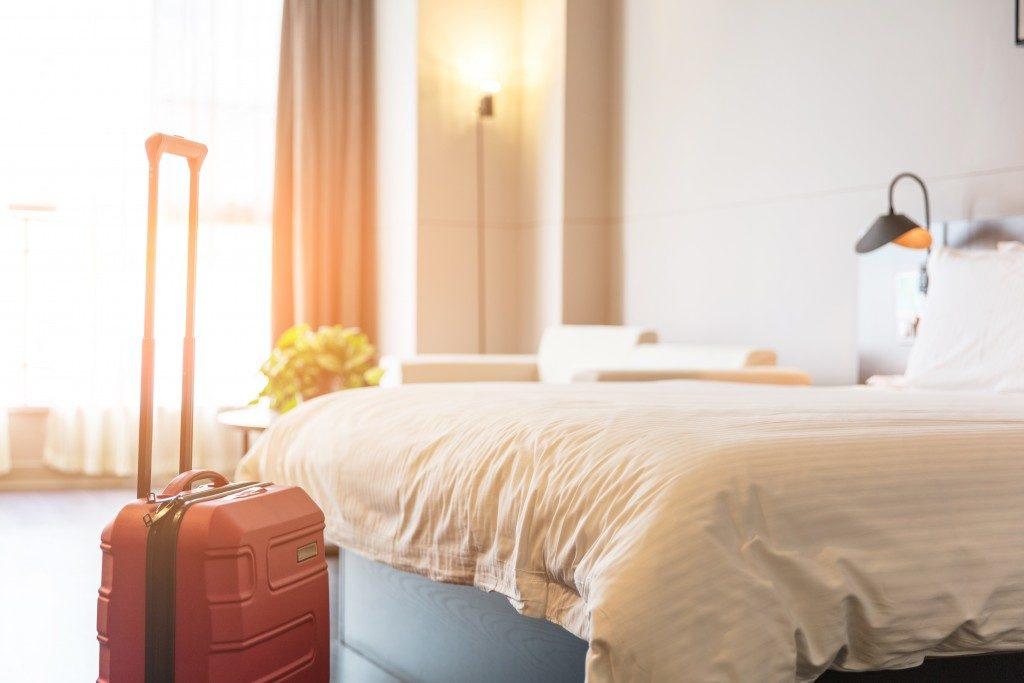 Luggage next to bed in guest room