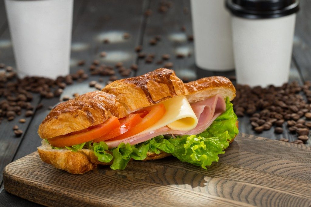 Croissant sandwich with ham, cheese and tomatoes on wooden cutting board