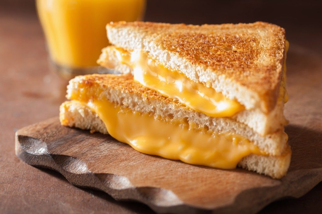 Grilled cheese sandwich on wooden chopping board