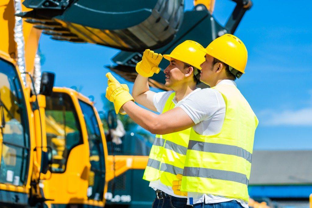 men at work looking at excavators