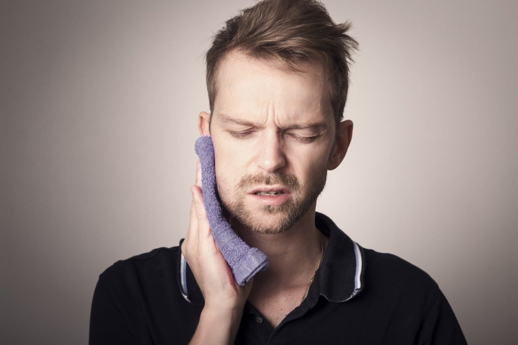Man experiencing pain from wisdom tooth removal
