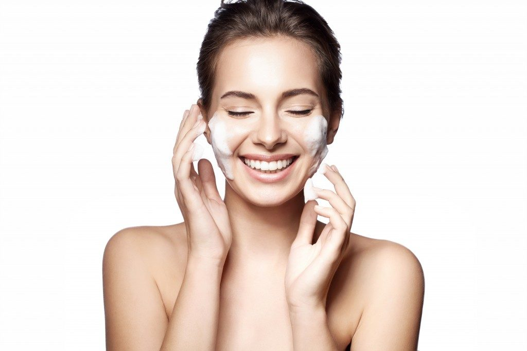Woman happy cleanses the skin on a white background isolated