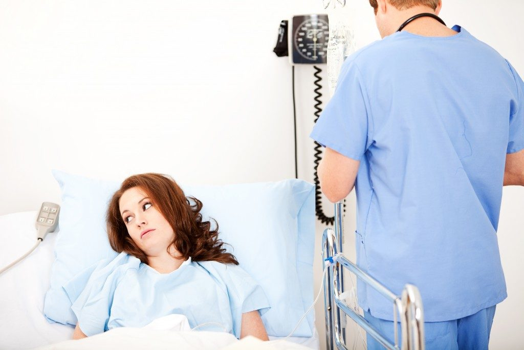 Female patient on hospital bed while the nurse checks on her
