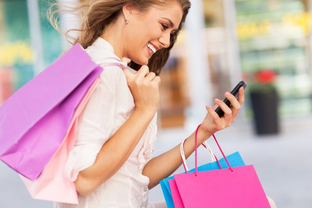woman looking at her phone and holding shopping bags