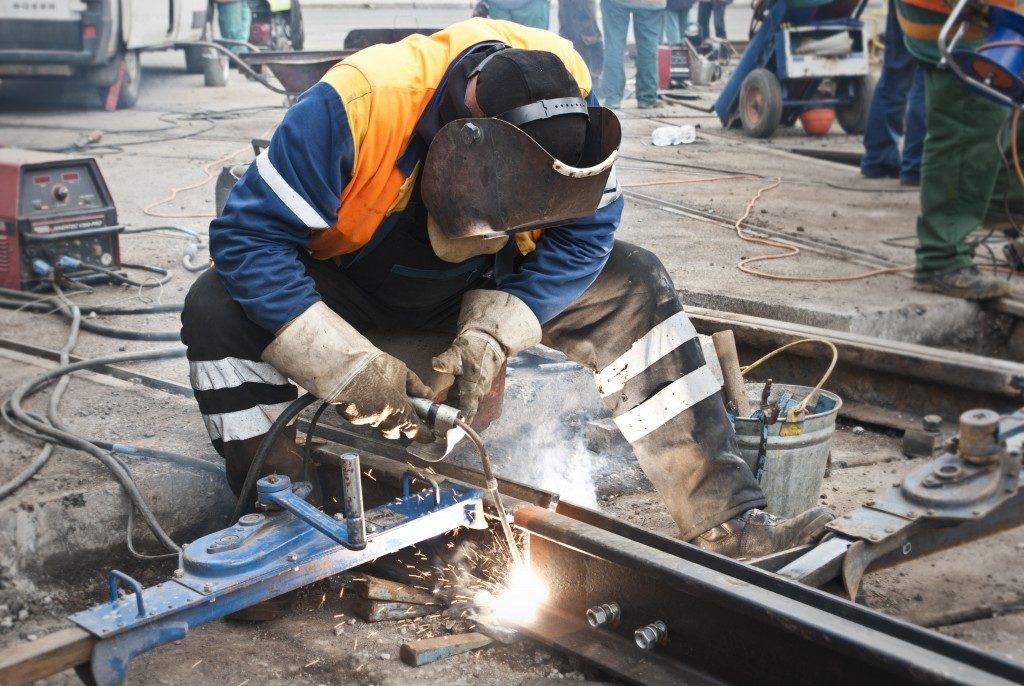 man wearing safety equipment while welding