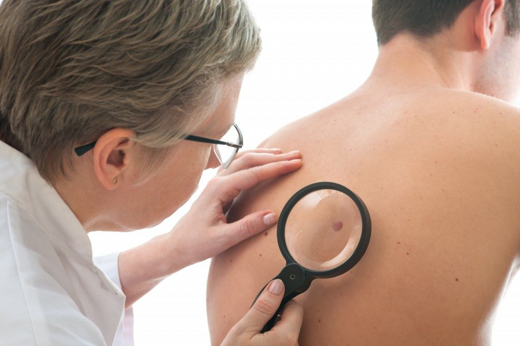 Dermatologist checking skin of patient
