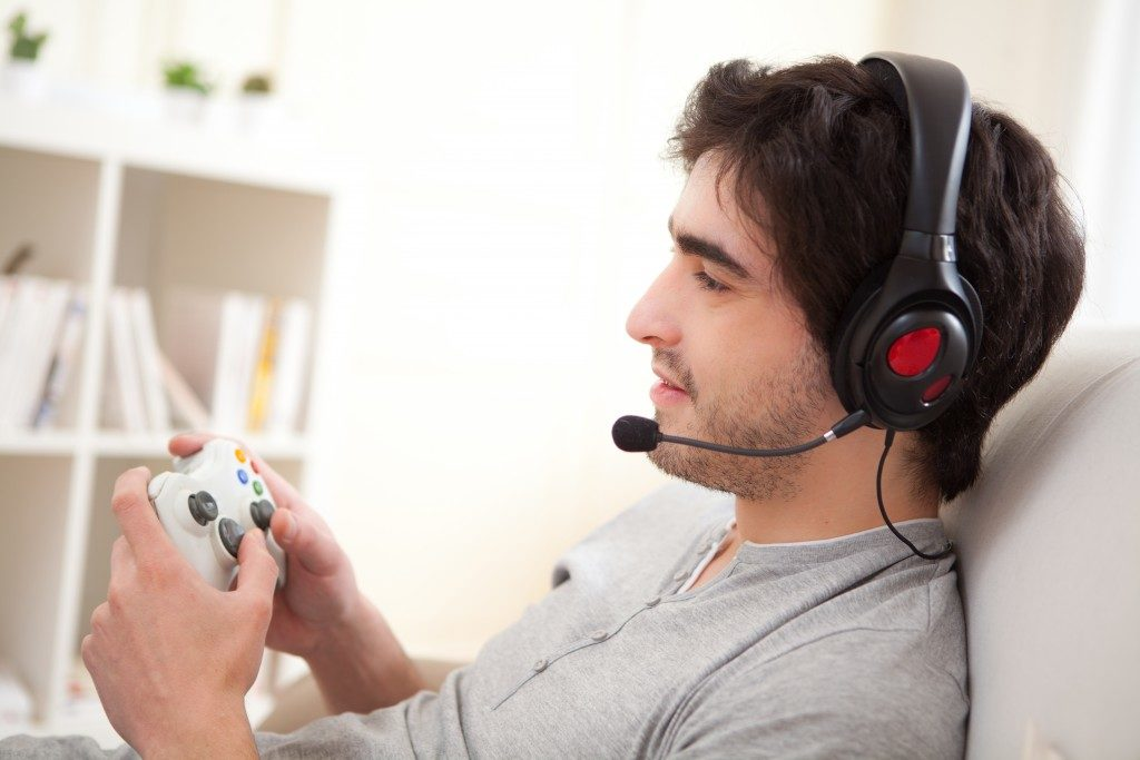 man playing video games in a sofa