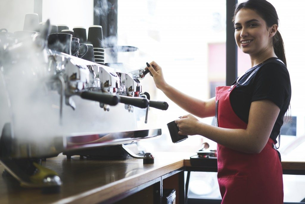 woman brewing coffee with machine