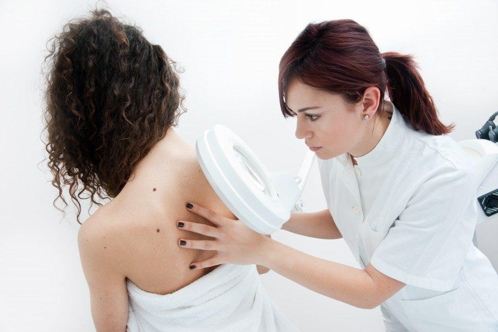 dermatologist doctor inspecting woman skin