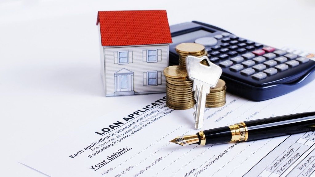 Fountain pen and key and calculator and paper house and coins stack on Loan Application form for Mortgage loans concept
