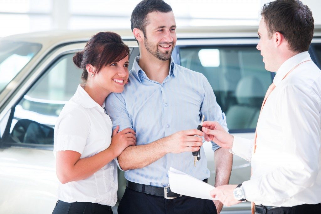 couple talking to a car salesman