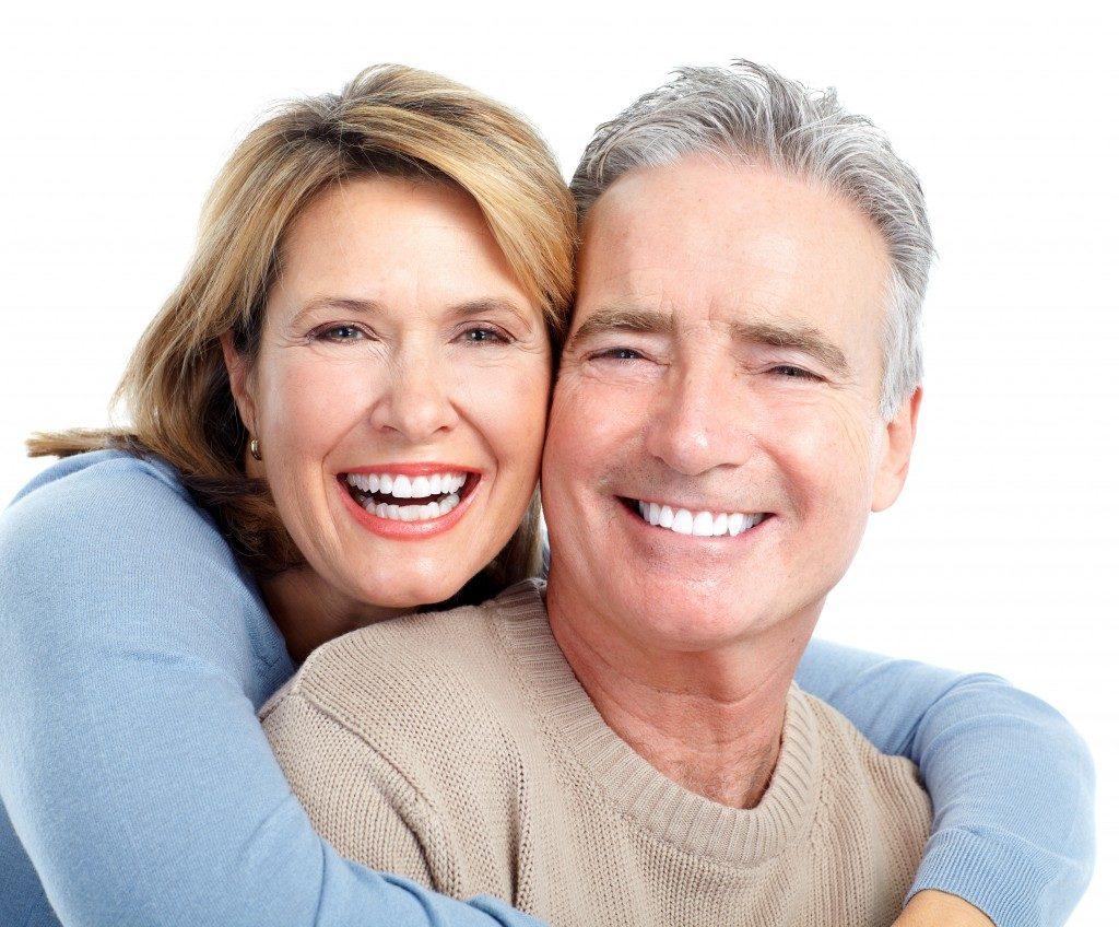Senior smiling couple over white background