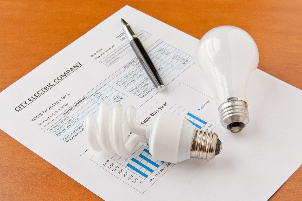 Energy efficient and incandescent bulbs on electric bill. Energy efficient house concept