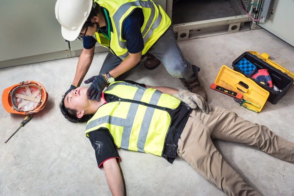 man checking his injured colleague's condition