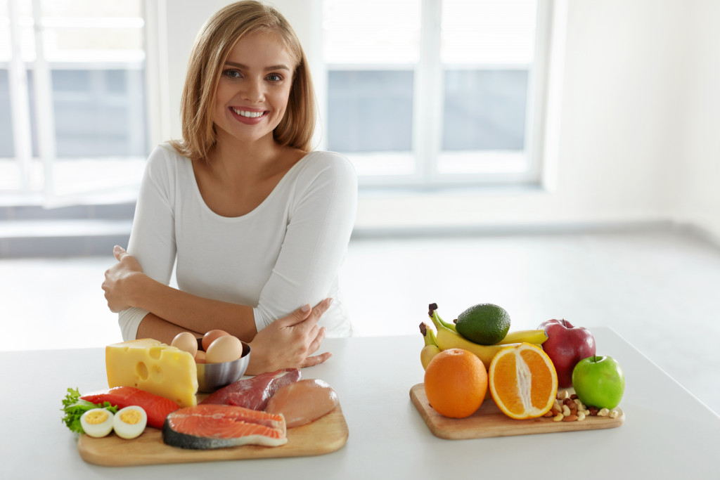 woman smiling with healthy food in front of her